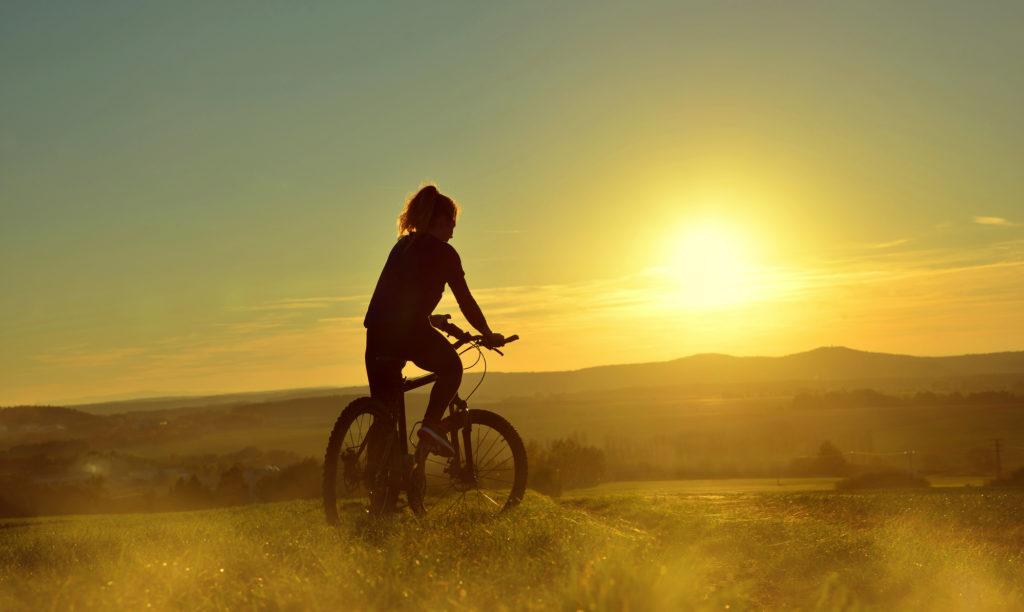 zlaki rowerowe w polsce - dziewczyna na rowerze, zachod slonca